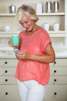 Senior woman using mobile phone while having coffee in kitchen