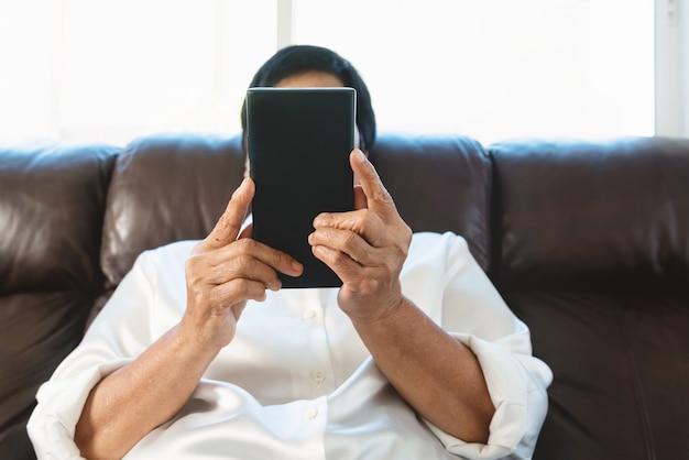 집에서 소파에 앉아 휴대 전화를 사용하는 수석 여성