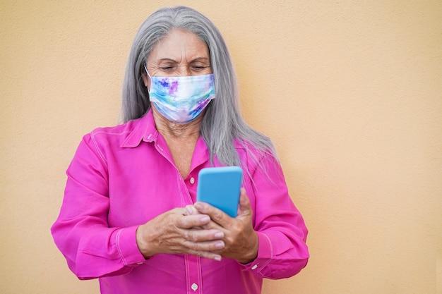 Старшая женщина с помощью мобильного телефона в защитной маске