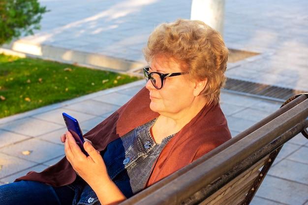 秋の天気のベンチで公園でスマートフォンを使用して年配の女性