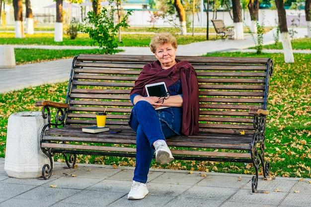 Пожилая женщина использует смартфон, читает электронную книгу, снимает музыку или получает онлайн-образование в парке на скамейке