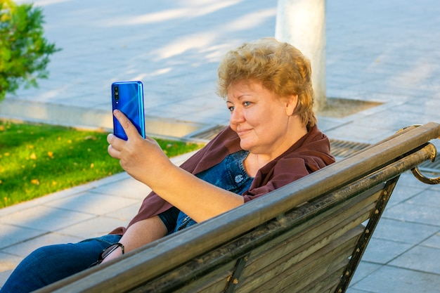 Senior woman using smartphone, read e-book, leasten music or take online education in park on bench