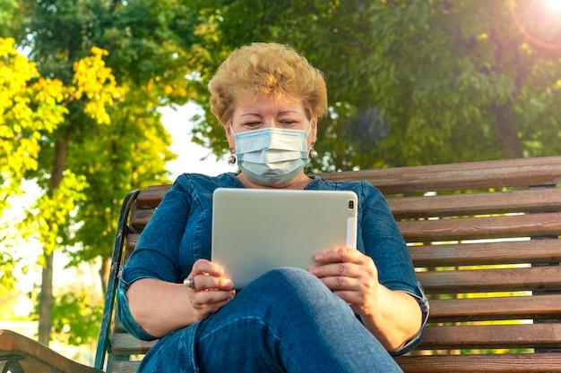 가을 날씨에 벤치에 공원에서 태블릿을 사용하는 수석 여자 전자 책을 읽고, 음악을 최소화하거나 벤치에 공원에서 온라인 교육을