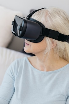 Senior woman in vr goggles on couch