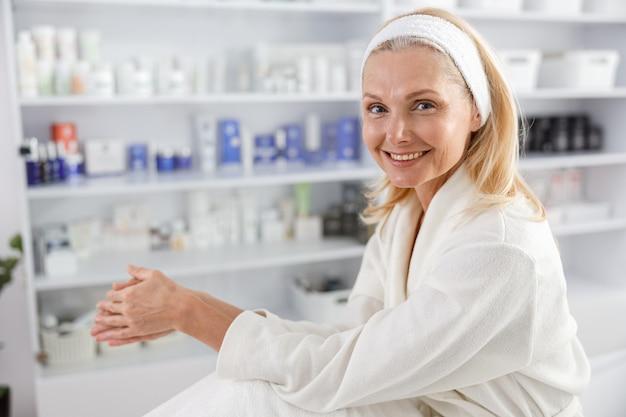 Старшая женщина ждет косметической процедуры в клинике эстетической косметологии.
