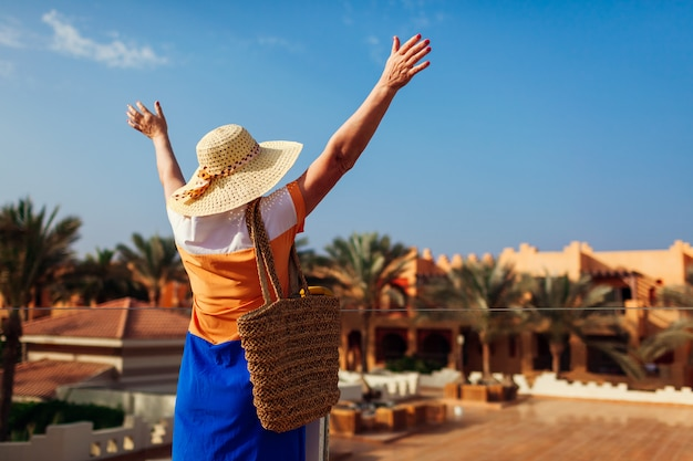 Senior woman walking on hotel territory and raising hands.
