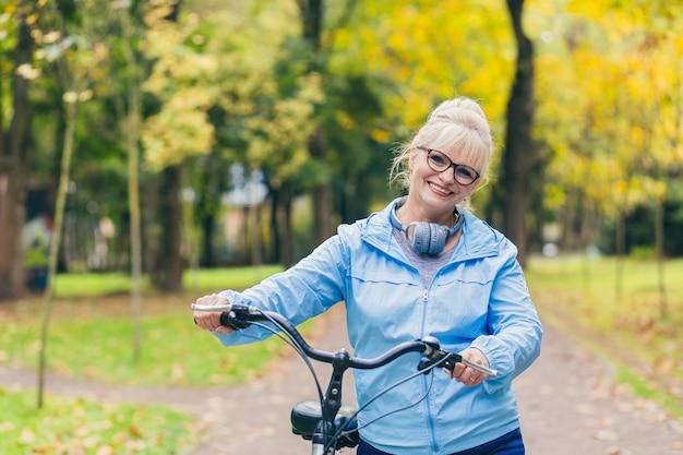 Старшая женщина гуляет в парке на велосипеде