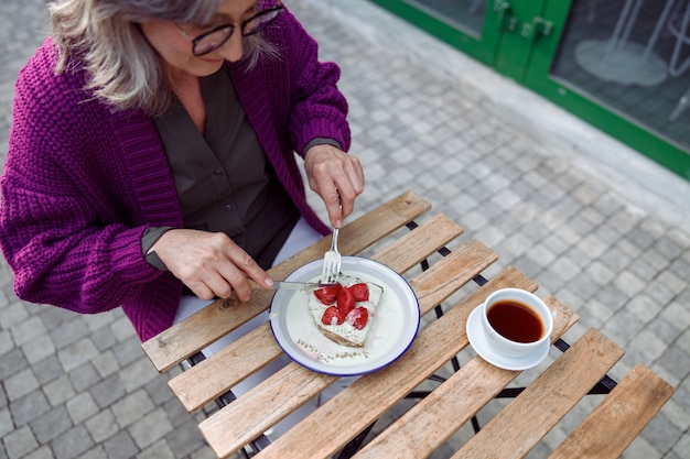 Senior woman in warm jacket eats toast with cream and strawberries sitting at table outdoors