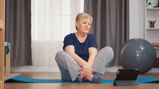 ヨガマットの上に座ってオンラインチュートリアルを見ながら肩を温める年配の女性。オンライン学習と研究、アクティブな健康的なライフスタイルスポーティな老人トレーニングトレーニングホームウェルネスと屋内エクササイズ