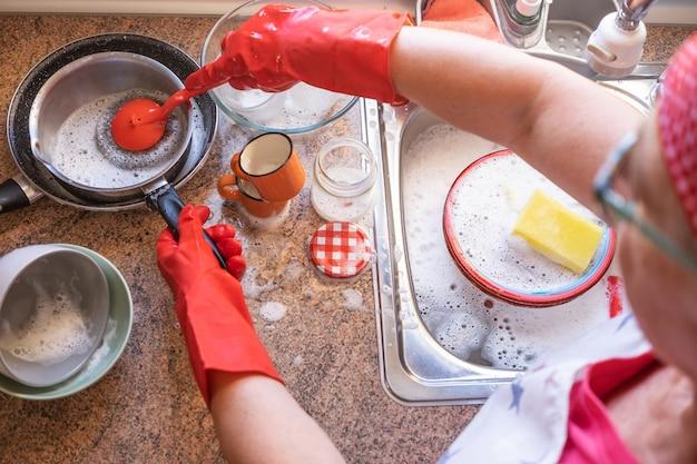 赤い手袋とバンダナを身に着けている窓の前で食器を洗う年配の女性