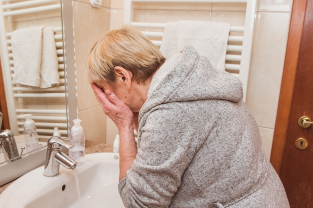 Senior woman washing her face at home
