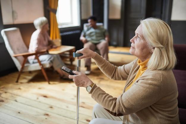 Старшая женщина смотрит телевизор в доме престарелых