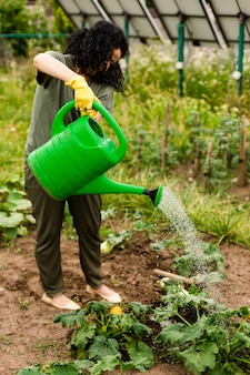 Senior woman watering the crops