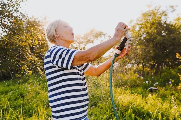庭の植物に水をまく年配の女性