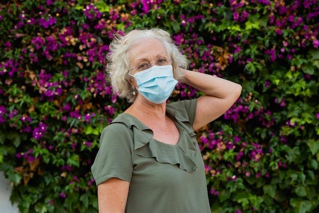 거리에서 파란색 수술 마스크를 쓰고 고위 여자