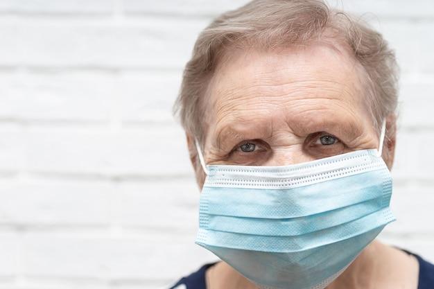 코로나 바이러스와 독감이 발병하는 동안 얼굴 마스크를 쓴 고위 여성. 질병 및 질병 보호. 코로나바이러스 예방을 위한 수술용 마스크. 아픈 노인 환자 기침.