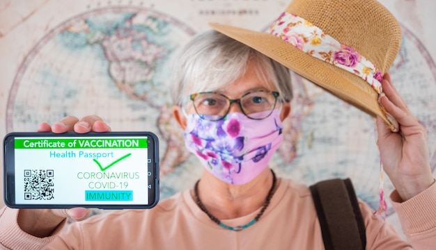 Senior woman wearing face mask shows health passport app for people vaccinated against coronavirus
