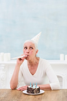 Senior woman wearing hat blowing party horn with tasty cake and candles on wooden table