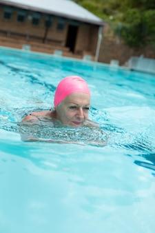 수영장에서 수영하는 동안 분홍색 모자를 쓰고 고위 여자