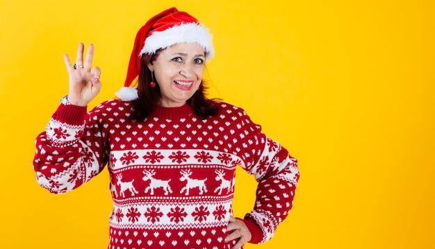 Senior woman wearing santa hat on yellow background, smiling