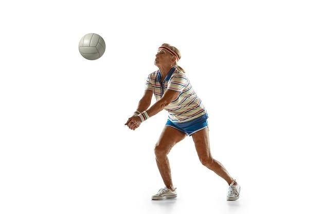 Старшая женщина в спортивной одежде играет в волейбол на белой стене