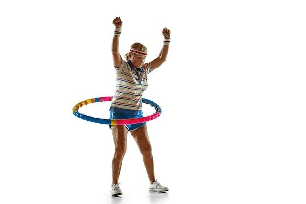 Senior donna che indossa abbigliamento sportivo formazione con cerchio sul muro bianco