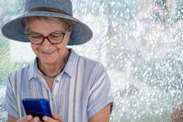 携帯電話の笑顔を使用してショッピングモールに座っている麦わら帽子をかぶった年配の女性