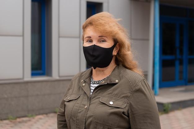 年配の女性は、感染症やインフルエンザ、ヘルスケアの概念に対する保護マスクを着用しています。コロナウイルス検疫。