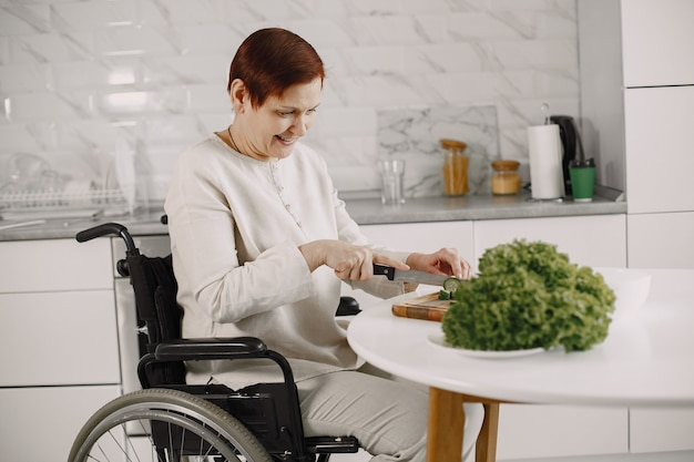 Senior woman in wheelchair cooking in kitchen. disabled people