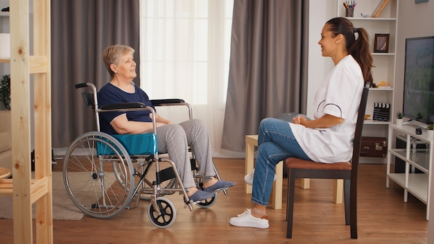 Senior woman in wheelchair having a conversation with nurse. old person retirement home, healthcare nursing, health support, social assistance, doctor and home service