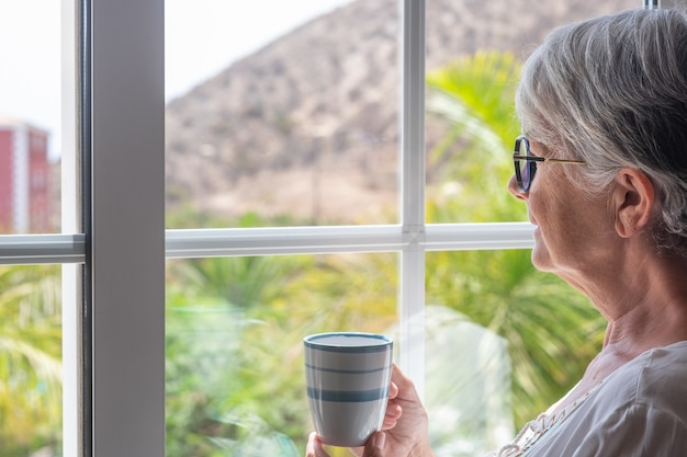 Senior woman at the window holding a coffee cup looking out