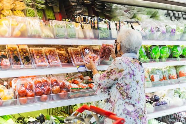 スーパーマーケットで保護マスクを持つ年配の女性