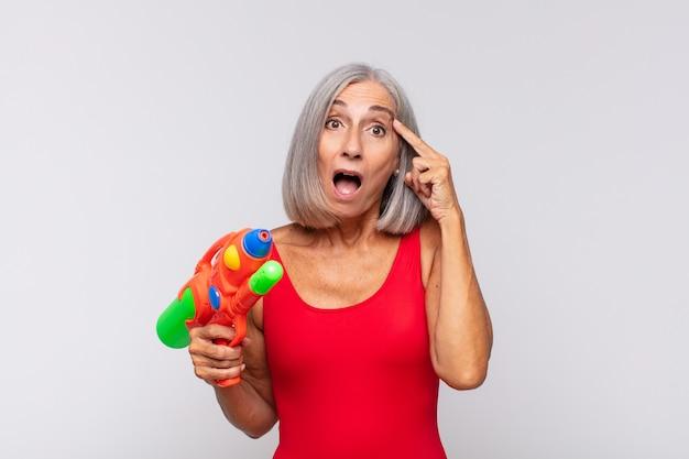 Старшая женщина с водяным пистолетом