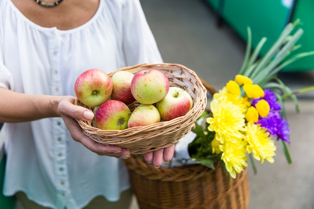 Senior woman with apples on market