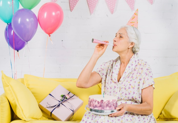 Senior woman with birthday cake blowing party horn