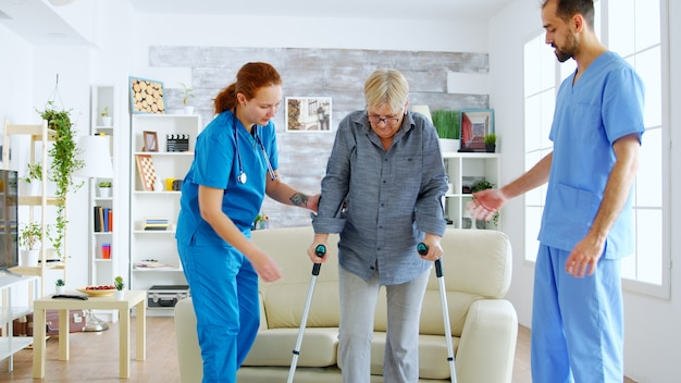 Senior woman with crutches getting help for female nurse and doctor to stand on her legs from the couch