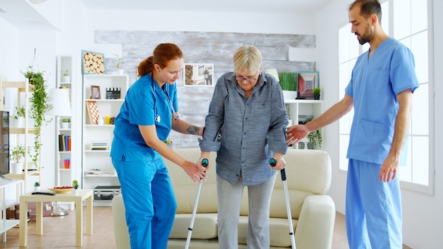 松葉杖を持つ年配の女性がソファから彼女の足に立つために女性の看護師と医師の助けを得る