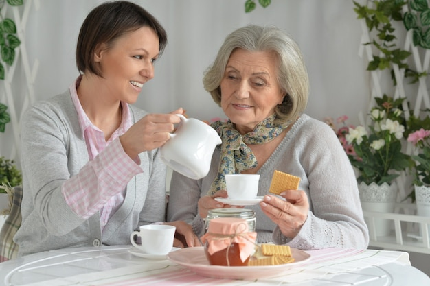 お茶と食べ物と娘を持つ年配の女性