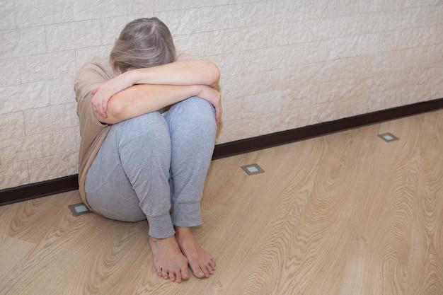うつ病の年配の女性は、床に座って悲しいストレスを感じます。
