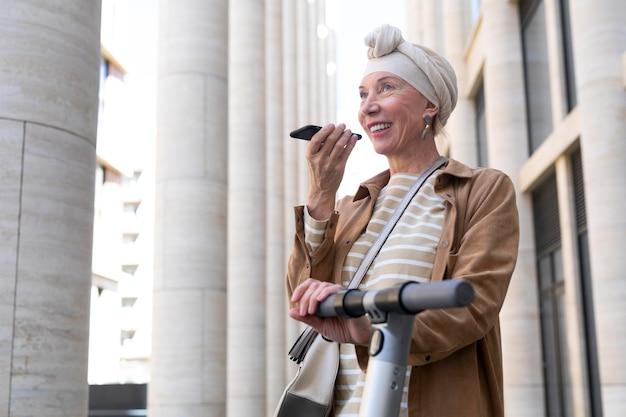 Senior donna con uno scooter elettrico parlando al telefono in città