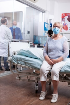 Старшая женщина с маской для лица против covid 19 сидит на краю больничной койки, ожидая врача с диагнозом болезни