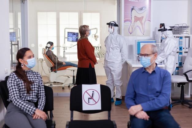 コロナウイルスによる世界的大流行時の安全対策として、口腔病学クリニックでppeスーツを着た歯科医と話し合うフェイスマスクの年配の女性