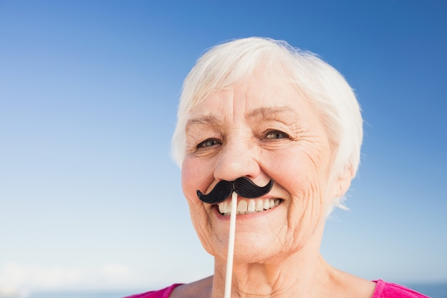 Senior woman with fake mustache
