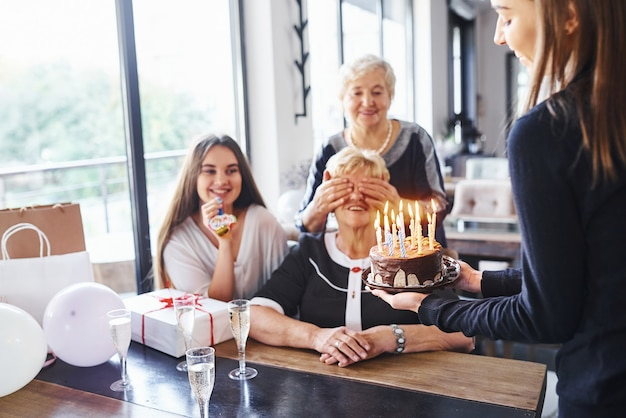Senior woman with family and friends celebrating a birthday indoors.