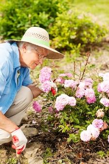 정원에서 꽃을 가진 고위 여자