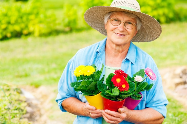 庭に花を持つ年配の女性