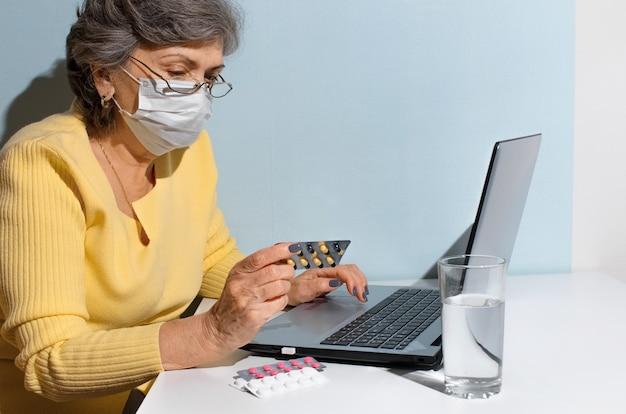 Старшая женщина в очках и медицинской маске, читая инструкции медицины. пожилая женщина с ноутбуком дома. концепция онлайн-консультации с врачом, новая норма.