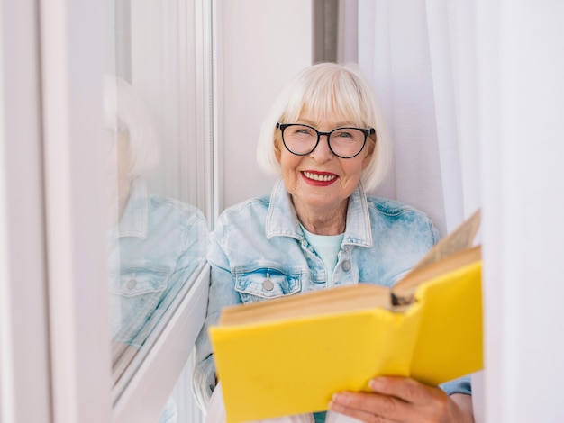 Старшая женщина с седыми волосами читает книгу у окна дома образование пенсия анти-возраст