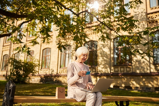 Senior woman with grey hair looking at her bankcard in front of a laptop while sitting near the hospital building