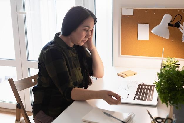 ノートパソコンを使用してホームオフィスで頭痛のある年配の女性。病気の老婦人。 covid-19検疫中に在宅勤務